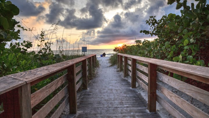 Photo taken from a wooden walkway leading out to the beach. In the foreground, there is a person sitting in a camping chair with a cooler at their side, looking out at the sunset.
