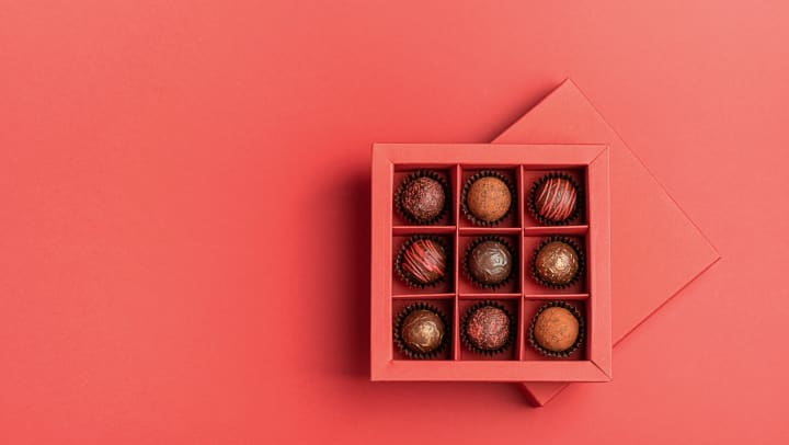 Chocolate candies in a red craft box on a bright coral background.