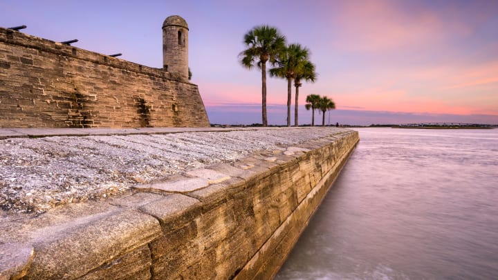 A view of the ocean at sunrise with a stone fort structure and palm trees