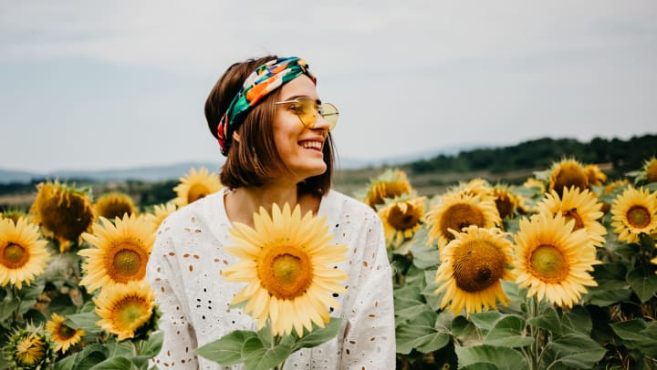 A smiling young woman enjoying a sunny day in a field of sunflowers.
