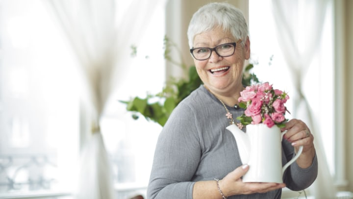 Senior woman holding a white pitcher with pink flowers in it and smiling.