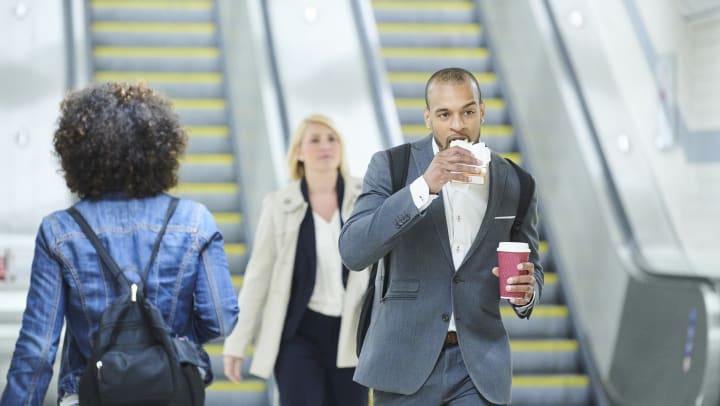 A man walking through a subway, holding a coffee in his left hand and eating a breakfast burrito with his right.