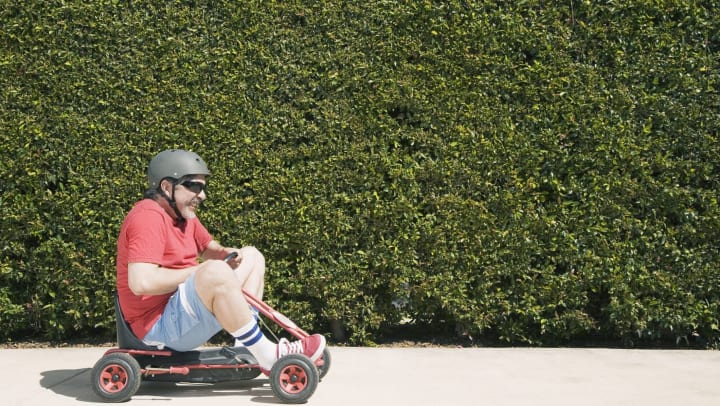 Man with a helmet on riding a tiny red go-kart on a sidewalk in front of  tall green hedges.