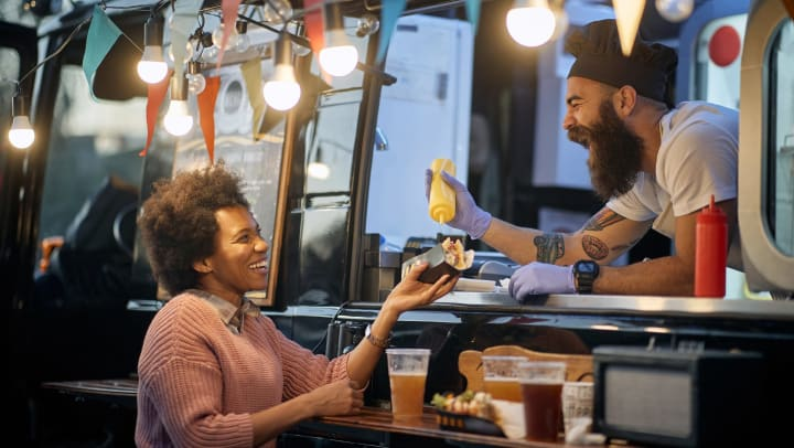 A man in a food truck putting mustard on a hot dog for a female customer.