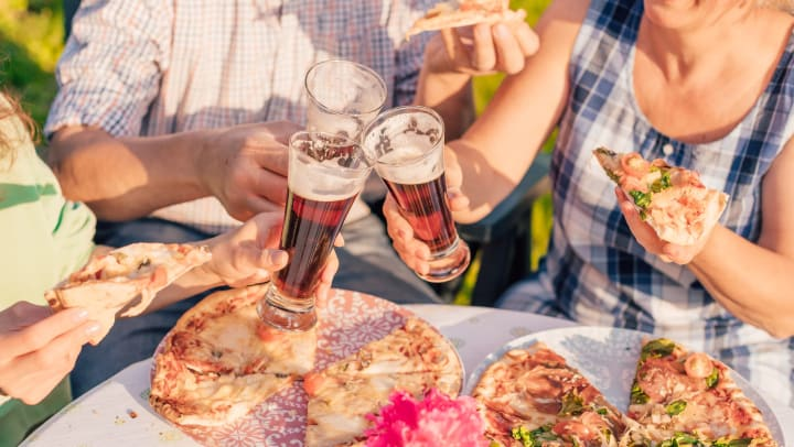 Three people at a table, toasting beers while eating pizza.