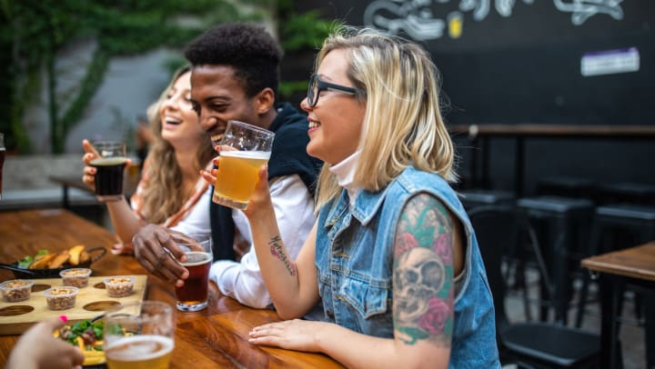 A group of smiling friends having fun while laughing and drinking beer on an outdoor patio.