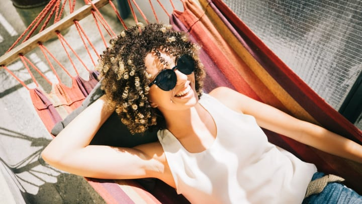 A smiling woman relaxing in a hammock on her balcony in the sunshine.