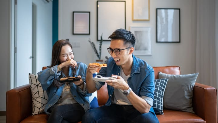 A young man and a young woman smiling, laughing, and eating pizza while sitting on a brown leather couch in an apartment with clean white walls