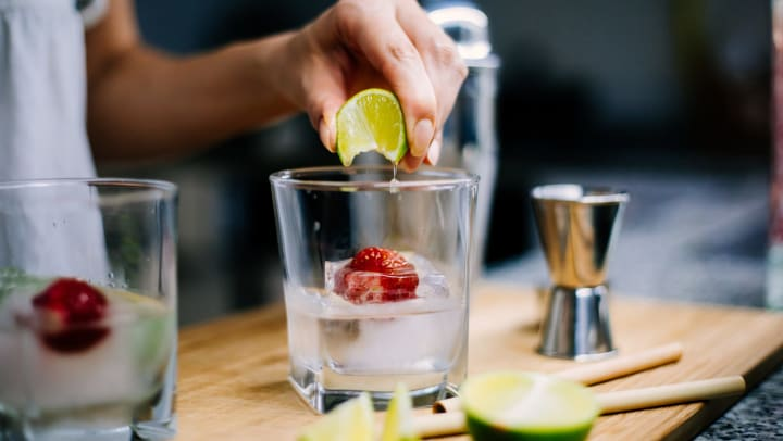 Person squeezing a lime into a glass containing ice and a strawberry.
