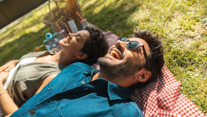 Man and woman lying on a checkered blanket in the grass with smiles on their faces and a basket in the background.
