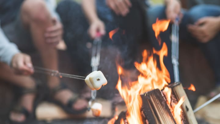 People sitting around a fire, roasting s'mores