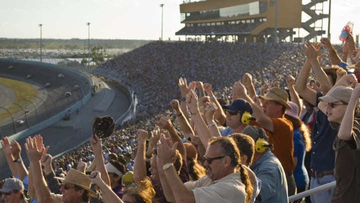 The crowd in the grandstand cheers at a car racing event.