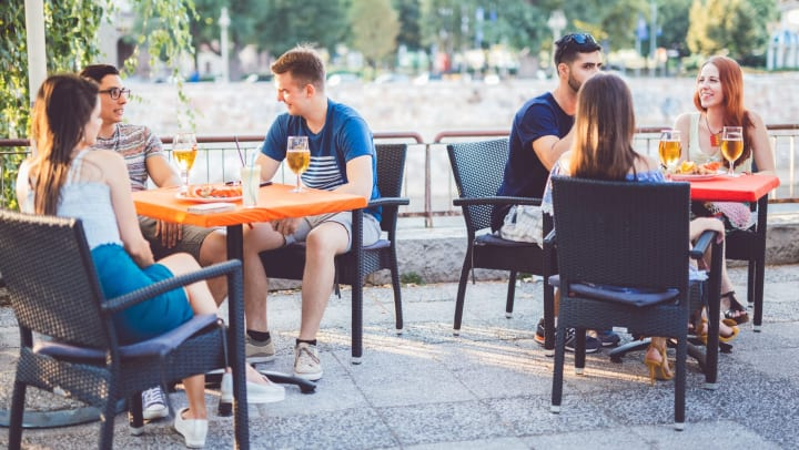 Young people seated at tables on a restaurant patio, enjoying drinks.