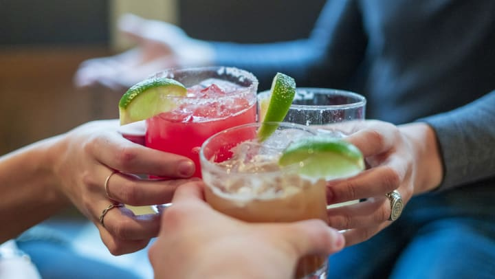 Close up of three people toasting fancy drinks in rocks glasses