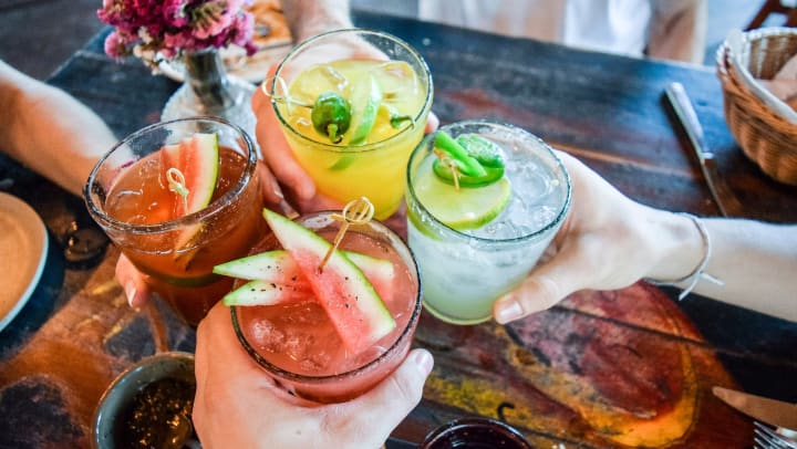 Four hands toasting with cocktails of different colors.