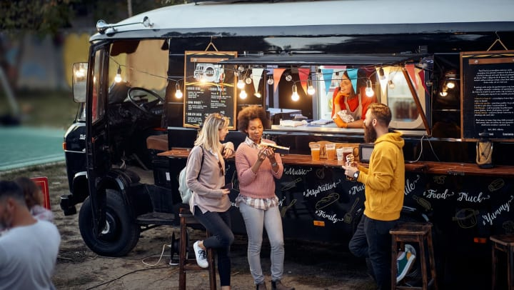 Two women and one man eating in front of a food truck.