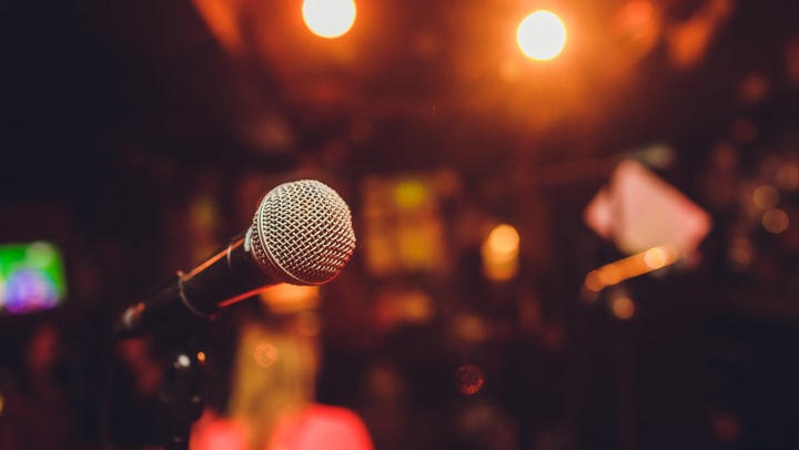 Close-up of microphone on stage with comedy club seating in blurred background.