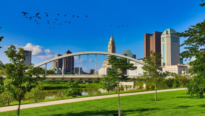 Landscape view of a lush green park and walking trail with a river, bridge, and city skyline in the background