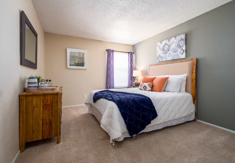Master bedroom with plush carpeting at The Fairway Apartments in Plano, Texas