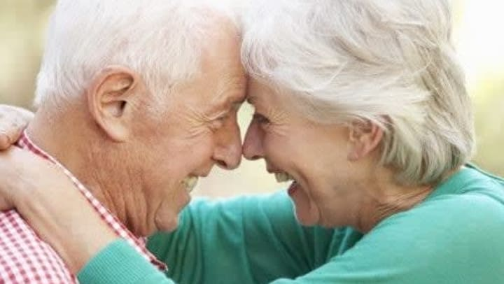 An elderly couple pressing their foreheads together affectionately