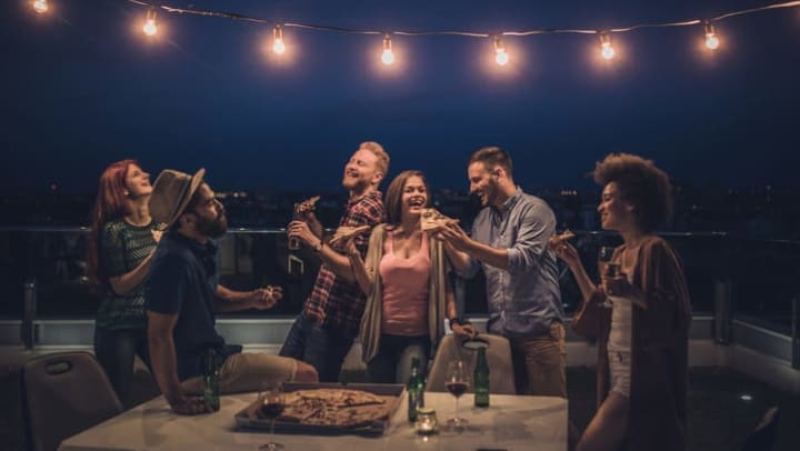 A laughing and smiling group of friends holding beverages and pizza, sit and stand around a table on a balcony, under a string of lights.
