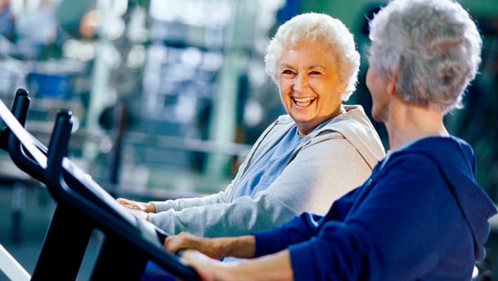 Two female seniors working out on the treadmill.