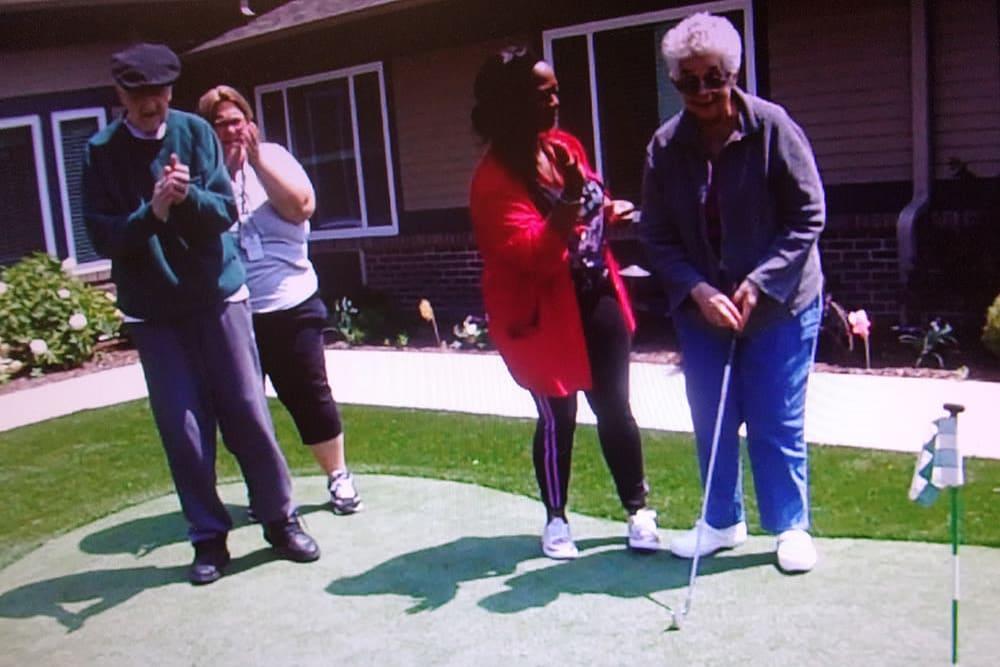 senior residents enjoying golf on the putting green