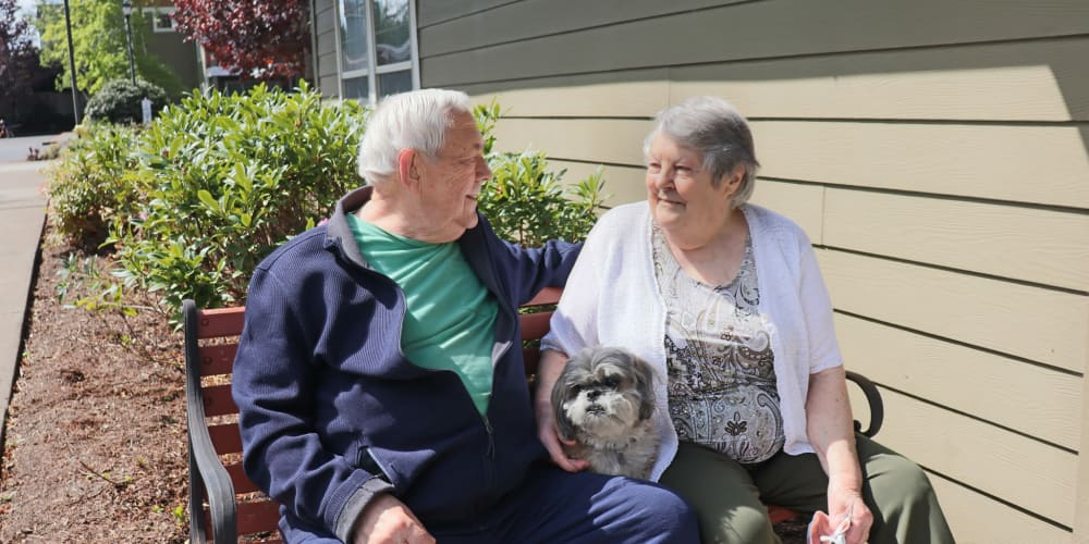 Residents enjoying sitting outside with their dog at The Springs at Clackamas Woods in Milwaukie, Oregon