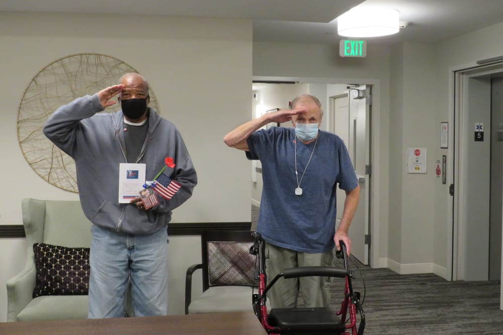 Two veteran residents standing and saluting at Aspired Living of La Grange in La Grange, Illinois