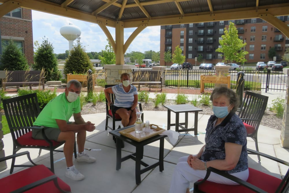 Group of residents sitting outside under a gazebo on a sunny day at Aspired Living of La Grange in La Grange, Illinois