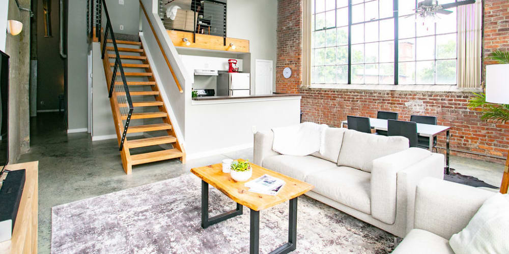 Cozy living room with exposed brick at Newnan Lofts Apartment Homes in Newnan, Georgia