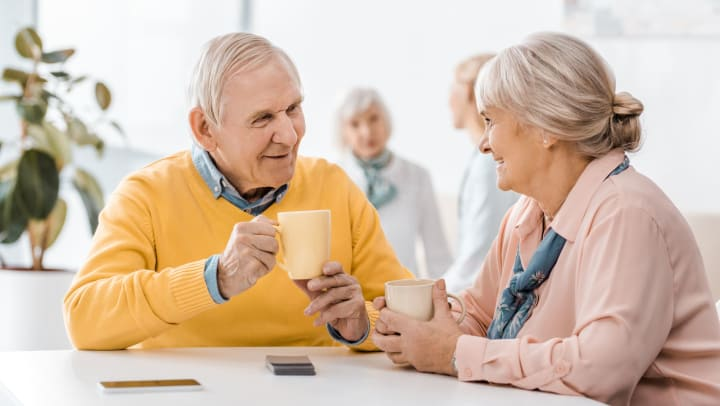 Elderly man and woman enjoying a hot beverage together.
