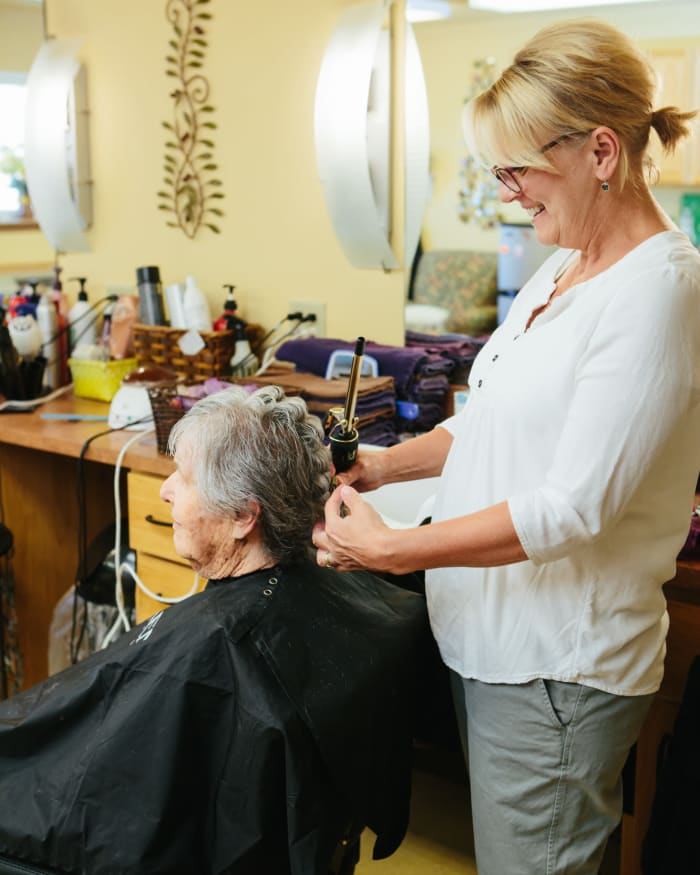 Resident getting her hair done at professional salon at The Springs at Missoula in Missoula, Montana