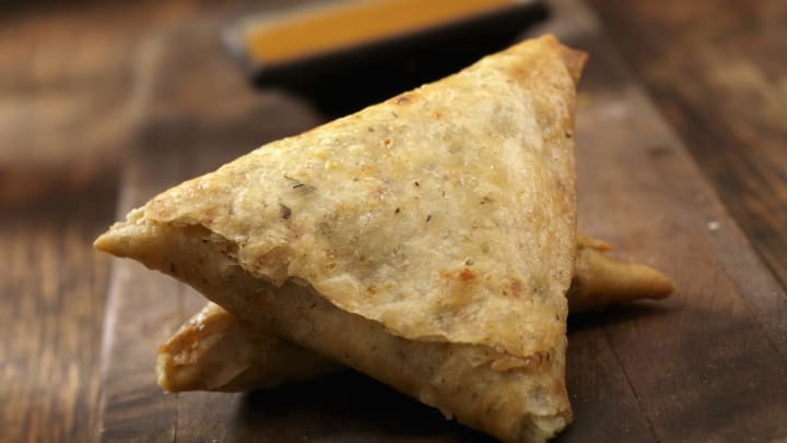 Two samosas with a container of sauce in the background