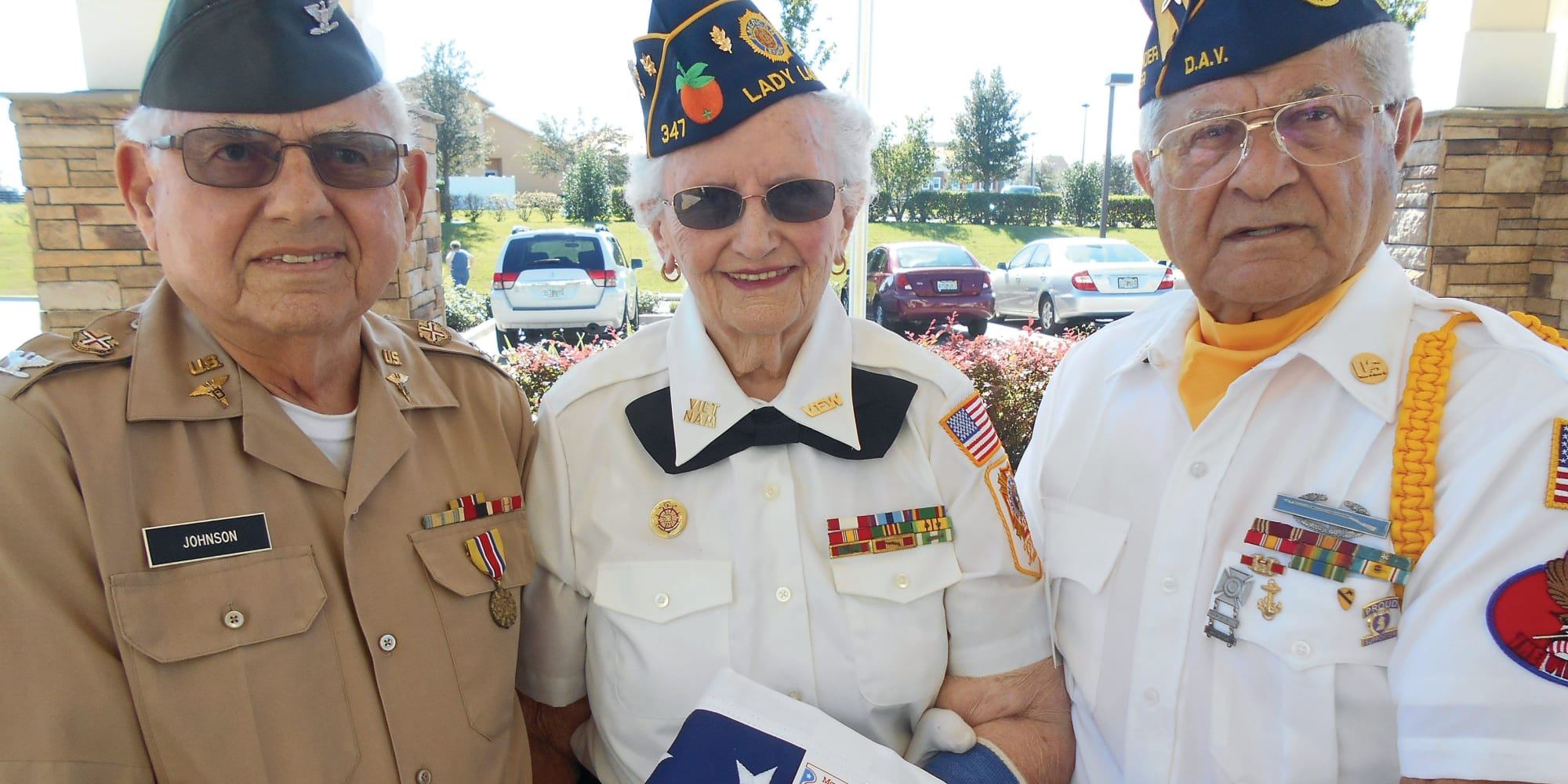 Three veteran residents holding a flag at Estrella Estates Gracious Retirement Living in Goodyear, Arizona