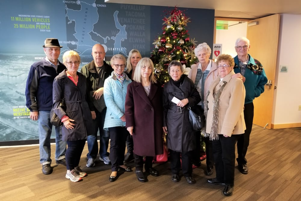 Group photo of residents by Christmas tree at Merrill Gardens at Burien in Burien, Washington.