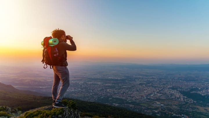 Man standing on the top of a mountain with a backpack with a yoga mat and looking through binoculars at a city below him.