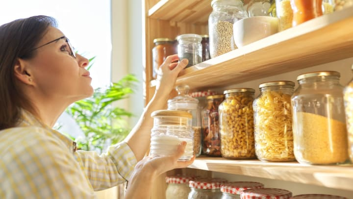 Resident reorganizing the pantry in her new home at Mosaic Dallas in Dallas, Texas