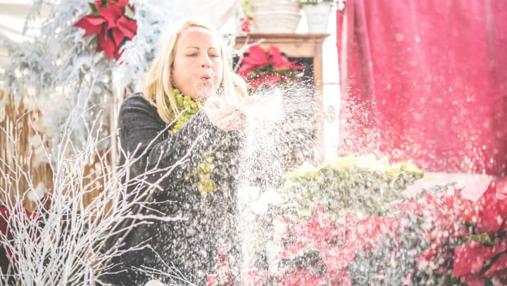 Woman blowing fake snow out of her hands at a Christmas fair
