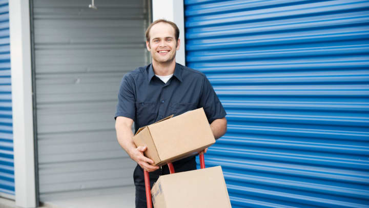Man outside self storage unit with boxes piled on a wheeled dolly.
