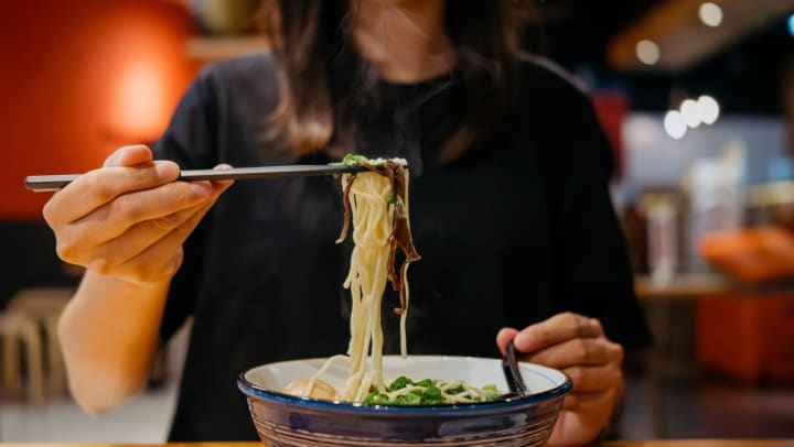 Young woman in a casual restaurant holding chopsticks and eating a hot bowl of ramen noodles