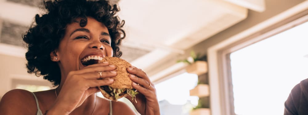 A woman takes a bite of a burger near M2 Apartments in Denver, Colorado