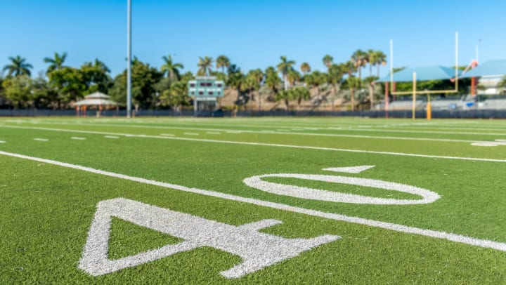 Ground-level view of an outdoor football field with palm trees in the distance and a clear blue sky