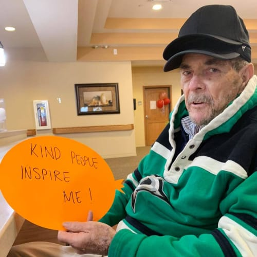Resident holding a piece of paper that says 'Kind People inspire me' at Oxford Glen Memory Care at Sachse in Sachse, Texas