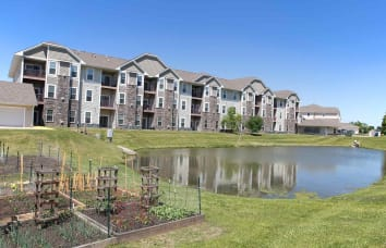 Apartment exterior and pond at Providence Pointe