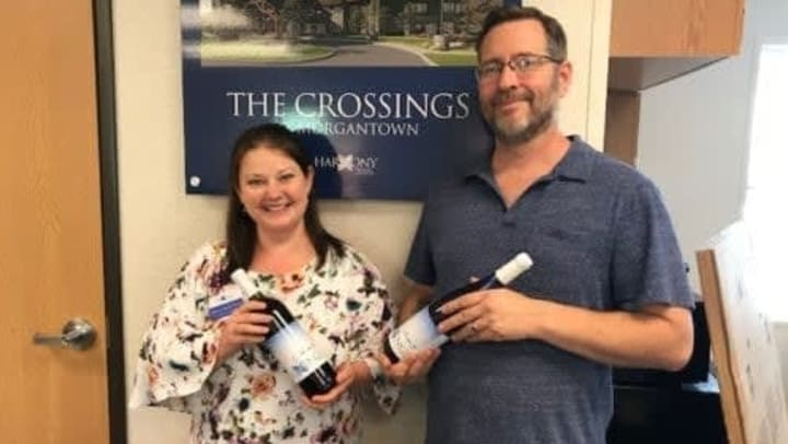 Two care givers holding bottles of wine