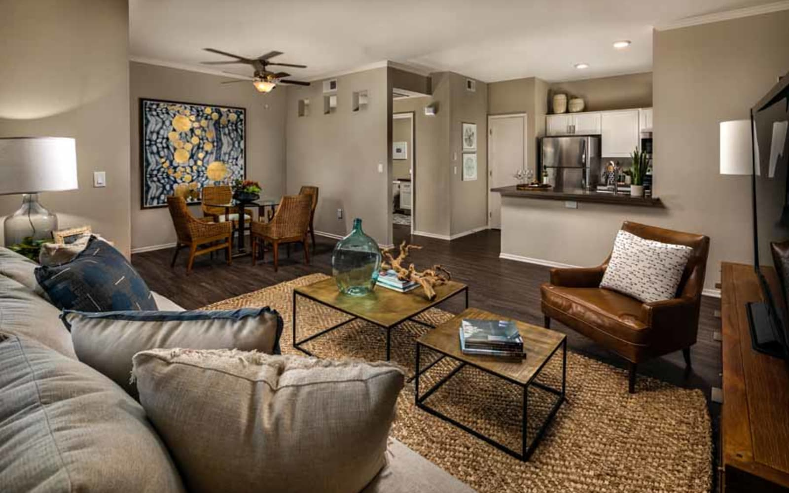 An apartment kitchen, living room and dining room at Castlerock at Sycamore Highlands in Riverside, California