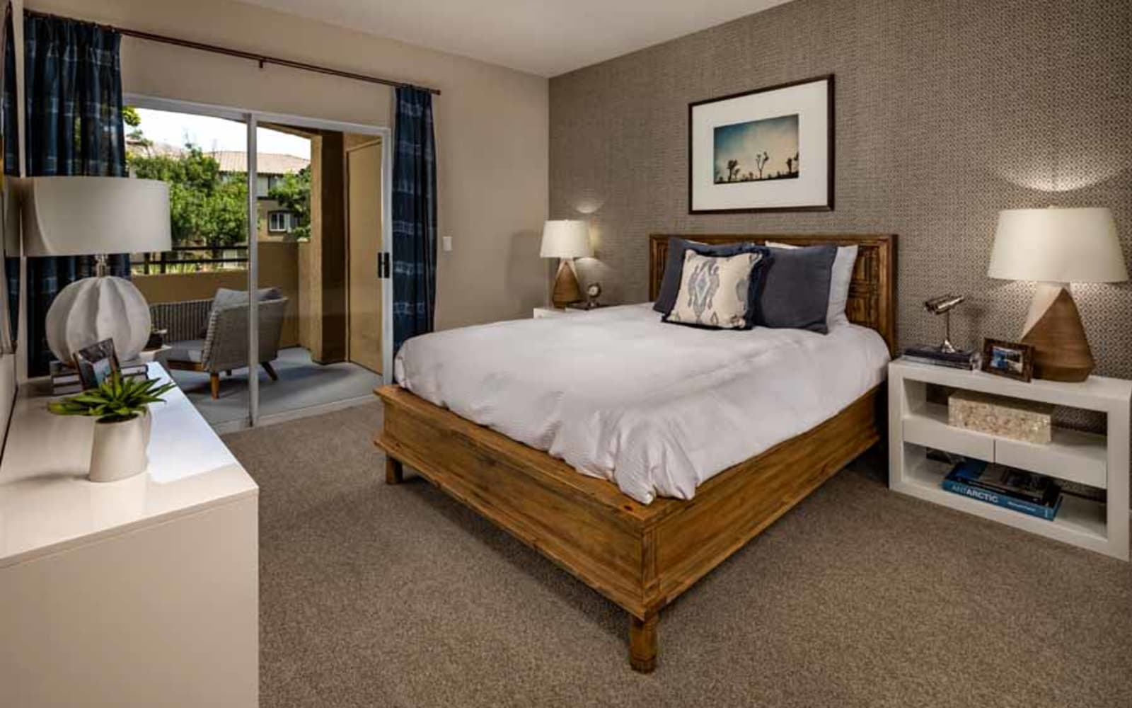 A spacious apartment bedroom with balcony access at Castlerock at Sycamore Highlands in Riverside, California
