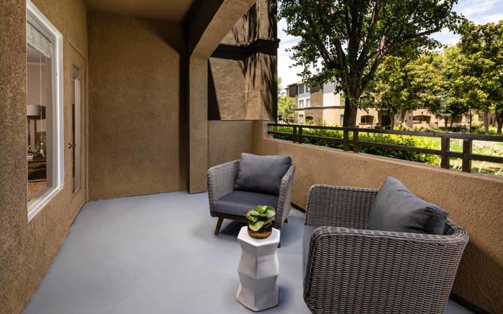 Outdoor seating on an apartment balcony at Castlerock at Sycamore Highlands in Riverside, California