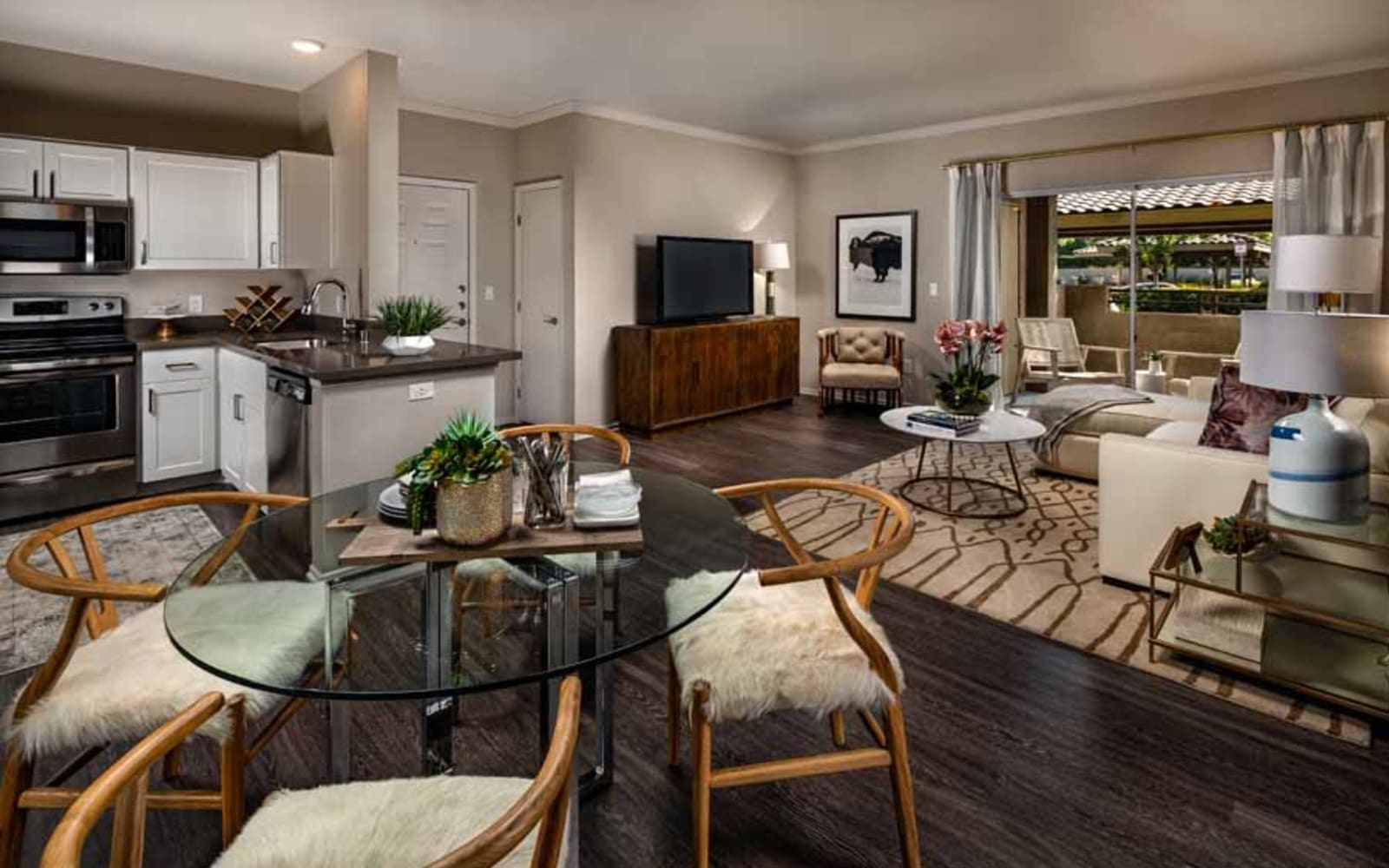 An inviting apartment living room, dining room and open kitchen at Castlerock at Sycamore Highlands in Riverside, California
